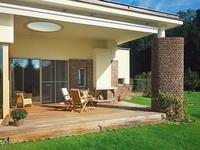 Jasne drewniane meble ogrodowe upiększą zielony ogród z tarasem